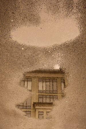 Vintage colors. Puddle reflection with houses, windows, sewer hatchs, street lanterns, trees without leaves. Grey asphalt surface