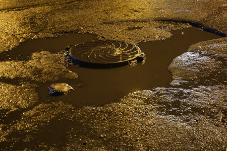 Sewage hatch in a dirty puddle on the asphalt. Night yellow brown light Stock Photo