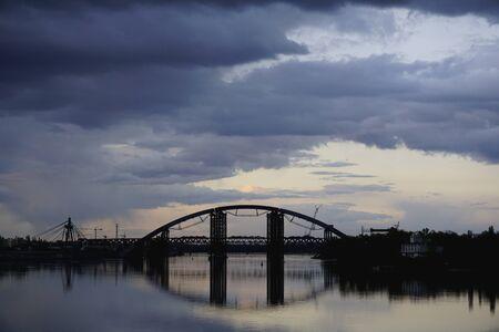 Bridge construction with reflection in river Dnieper, Kiev, Ukraine. Ukrainian landscape, Dnipro, Kyiv. Stormy dark blue clouds.