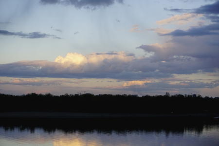 Landscape with forest and amazing sunset blue clouds reflected in river Dnieper, Kiev, Ukraine. Dnipro, Kyiv.