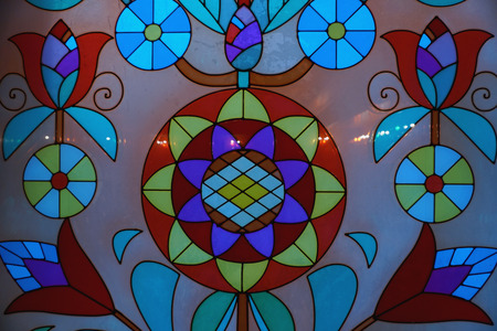 Colored stained-glass window with round colorful flowers with leaves