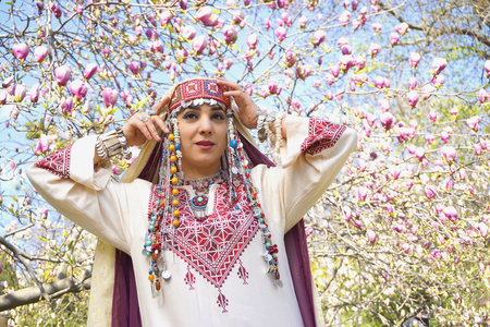 Pretty girl against of magnolia flowers in national Palestinian costume with head covered. Botanical garden.