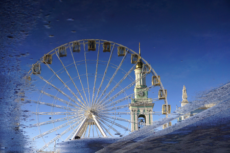 Inverted reflection in a puddle. Ferris wheel on the background of the bell tower and the blue sky. Kiev, Kyiv, Ukraine.
