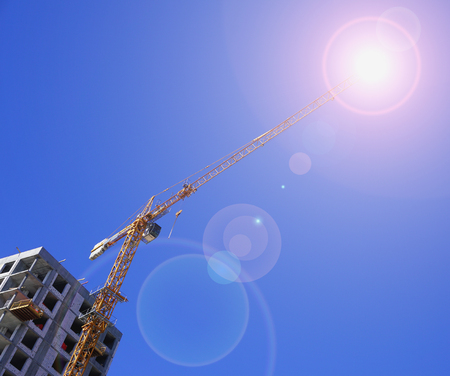 Yellow construction crane isolated with unfinished building, sunny glare, sunlight against a blue sky background