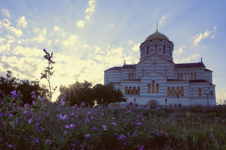 St. Vladimirs Cathedral, Chersonese, Sevastopol, Crimea, Russia. Sun with long rays and field with little purple violet flowers
