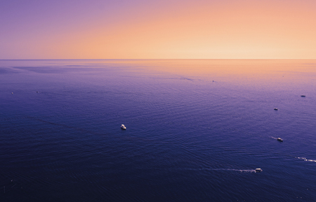 Violet yellow orange purple Black sea at sunset time, pleasure boats with tourists. Freedom concept, calming water background