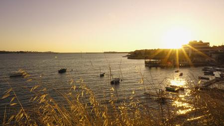 Black sea with fishing boats at yellow sunset time with bright sun. Sevastopol, Crimea, Russia. Foto de archivo