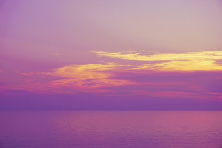 Violet lilac pink purple yellow sky with amazing clouds over Black sea. Calm sea background, colorful sunset time today.