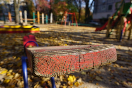 A playground with a red shawl for two children. Old peeling paint, sunny golden autumn. Yellow leaves lie on the ground under your feet .