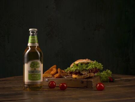 Somersby Apple Cider by Danish brewing company Carlsberg Group with fast food burger on a round wooden table. St.Petersburg, Russia. 2020-02-21. Éditoriale