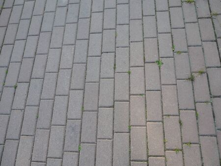 Details of gray brick stone pavement on the street road. Gray stone blocks background and texture, paving slabs.