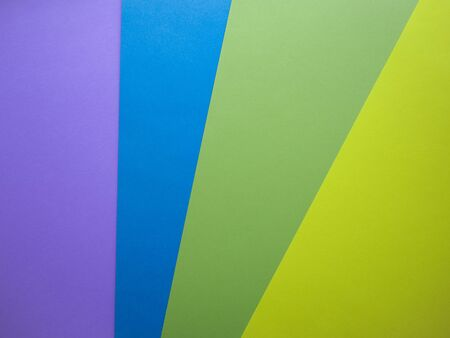 Different colors paper top view abstract background. Violet, blue, green and yellow cardboard paper sheets. Stock Photo