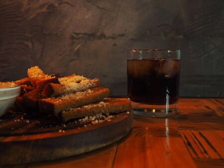 Glass of cold whiskey with ice on a wooden table in the dark bar, fried croutons with cheese on a wooden cutting board with creamy tartar sauce in a small bowl on a grunge background.