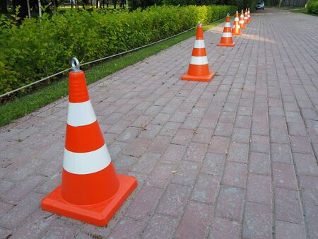 Orange and white striped traffic cones chained together. It is used as a fence when carrying out road-building works, for demarcating traffic or for designating emergency sites and road accidents.