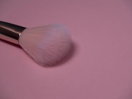Pink make up brush for applying powder and blush on a pink background. Professional makeup artist tool close up. Imagens