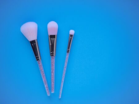 Pink makeup brushes on a blue background top view with copy space. Set of powder brush, blush brush and eye shadow brush for professional make-up.