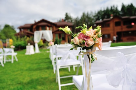 dcor: Green lawn with white chairs and festive dcor for wedding ceremony