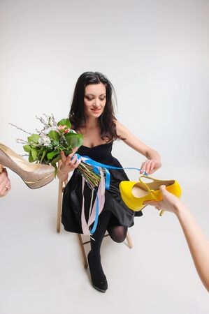 buying questions: Girl in black dress chooses shoes for his party Stock Photo