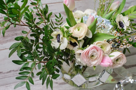 Close up of bouquet of ranunculus, anemones and other flowers in a vase of glass stands on the background of vintage floor. Archivio Fotografico