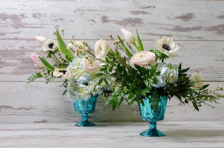 ラナンキュラス、アネモネ、他 2 つの青い花瓶に生花のブーケを 2 つは、ビンテージの床の背景に立っています。