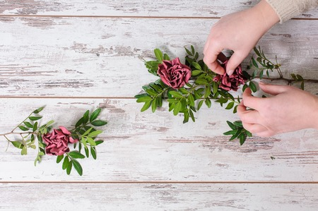 gathers: Florist gathers a bouquet with their hands  on vintage background Stock Photo