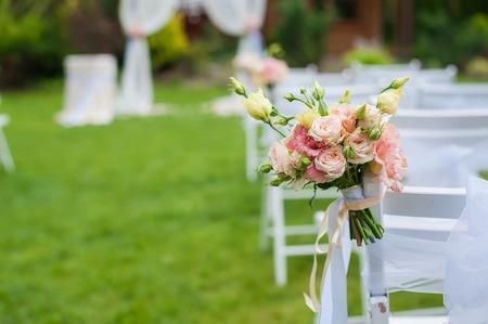 緑の空き地は、結婚式のために準備に立っている白い椅子。椅子は、花の花束で飾られています。背景がぼやけています。 写真素材