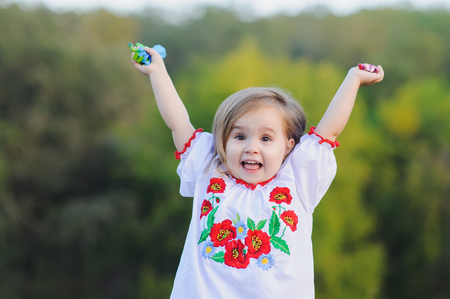 rejoices: Little 3-year-old girl raised her hands up and emotionally rejoices. A girl dressed in white Ukrainian national dress with embroidered flowers.