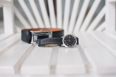 mans watch: Mens Wrist Watch with leather strap mens belt and lie on a white wooden chair. Stock Photo