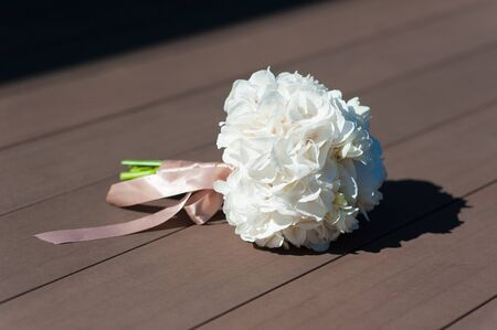 constricted: Bridal bouquet on a brown background or gender. The sun shines on the living flowers in outdoors. Bunch constricted pink ribbon.