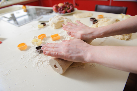 beaten: Close-up of woman hand with a rolling pin baking cookies. dough, flour, baking tins on a white table in the background. Stock Photo