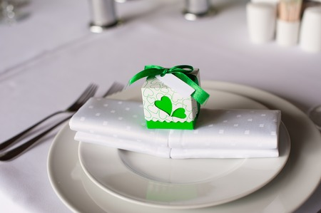 bonbonniere: Bonbonniere with green tape and heart on the side on plate on wedding table.