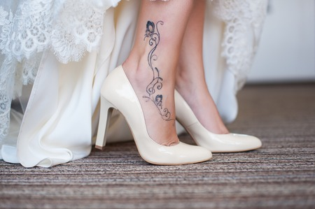 Bride in white wedding dress shows beautiful slender legs with tattoo in white shoes