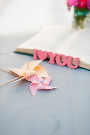 part of me: Dos molinetes en un vector. letras de madera hechos a mano de color rosa borrosa Te amo, libro y un ramo de flores en el fondo. Centrarse en molinete. Foto de archivo