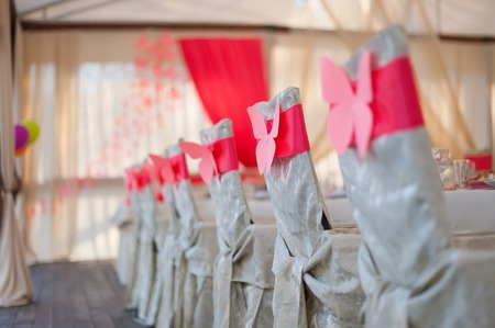 butterfly bow: Chairs in the white covers around the table. On the backs of chairs and red ribbon bow in the form of a butterfly. indoors
