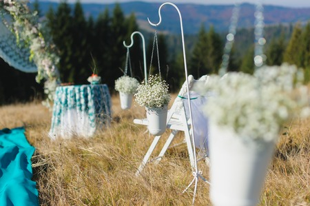 Happy outdoor wedding ceremony scene for autumn mountain wedding. Wedding aisles decorated wedding arch, table, chair decorations of flowers, gypsophila, mountains in the background.