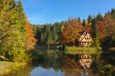 The scenic landscape. house by Lake. Reflection in water. Forest and mountains surround the house. autumn. Stock Photo
