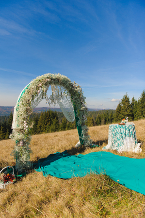 aisles: Happy outdoor wedding ceremony scene for autumn mountain wedding. Wedding aisles decorated wedding arch, table, chair decorations of flowers, gypsophila, mountains in the background.
