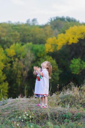 three year old: screaming, smiling three year old girl raised her hands  and looks at the sky. girl dressed in white Ukrainian national dress with embroidered flowers.