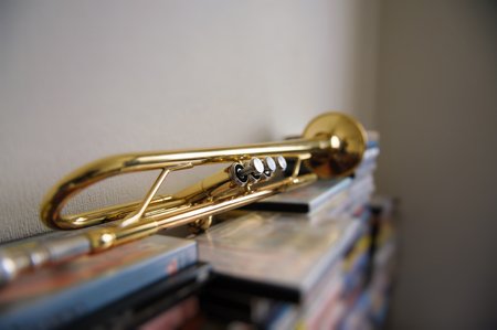 lays: Old trumpet lays on a stack of DVD boxes in the room. Selective Focus.