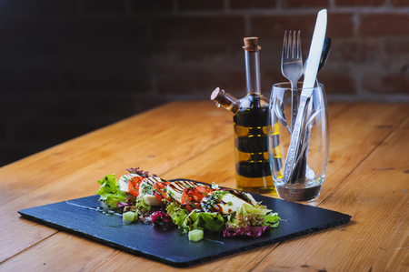 glass brick: Caprese - Italian salad with cherry tomatoes, olives and mozzarella cheese and basil on a black plate. Cutlery sets in a glass. Brick wall in the background. Stock Photo