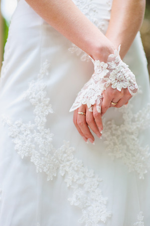 lace gloves: Hands bride stacked together on lace dresses. Focus on hands, manicure,  lace gloves and ring. Stock Photo