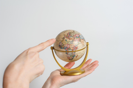 forefinger: Female with small desktop globe of planet earth in hand. Forefinger pointing to Europe. White background.