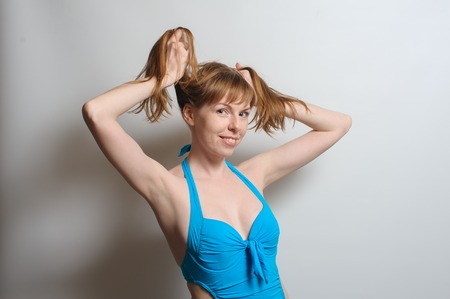 Joyful beautiful redhead woman without makeup making pigtails, smiling happily at camera, wearing blue swimsuit. White background.