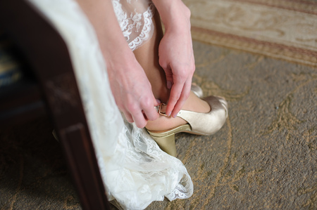 staging: Bride puts on a shoes to a foot standing in a room on a brown floor. Woman buttons white shoe. Stock Photo