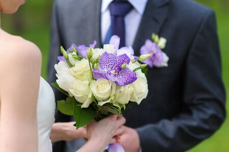 holding close: Bride and groom holding bridal white rose bouquet close up Stock Photo