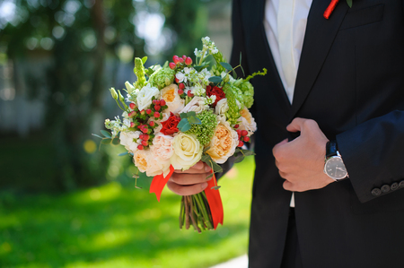 alliances: Groom in a black wedding suit holding a beautiful flowers bouquet. Stock Photo