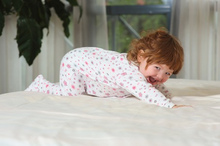 bed clothes: Smiling toddler girl playing in a night clothes on the bed in the bedroom with white linens. Happy curled red-haired baby. Stock Photo