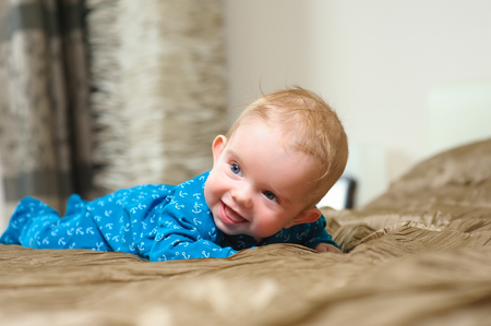 mouth cloth: Baby boy lying on belly. Cute year-old kid with interest looks and smile, boy lying on bed in the bedroom with white linens. Home interior in the background.