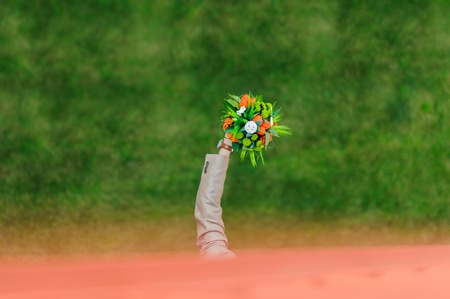 outstretched hand: A man holding a bouquet. Hand holding bunch of flower against green background. Green lawn. Groom with outstretched hand side. View from above. Stock Photo