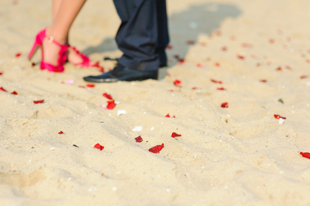 hugging legs: Legs of young hugging or kissing couple standing on sand, beach. Pretty rose petal strewn on the sand. Girl in red shoes, a man in trousers. Wedding ceremony on the beach.